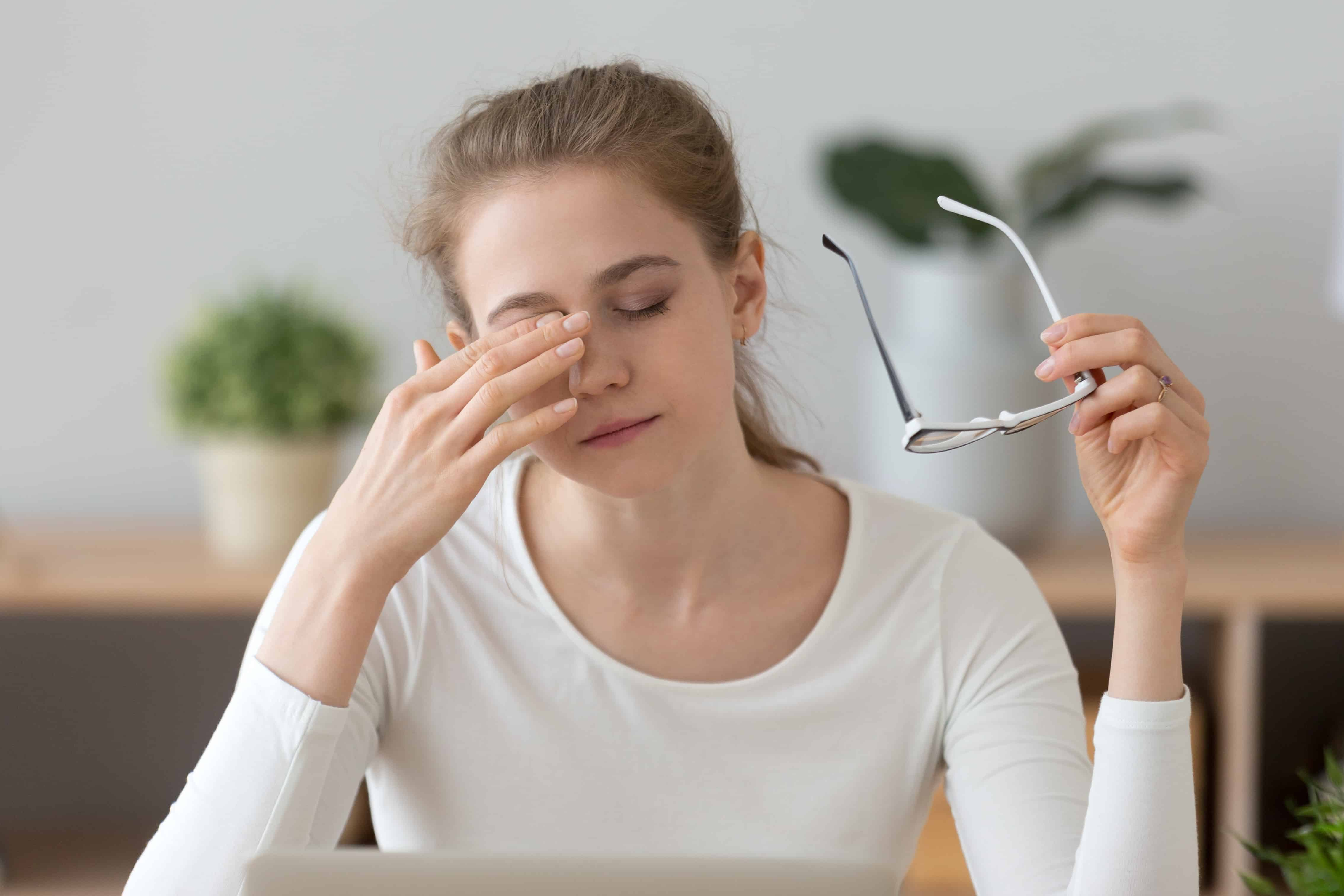 Fatigued girl taking off glasses rubbing eyes feeling eye strain