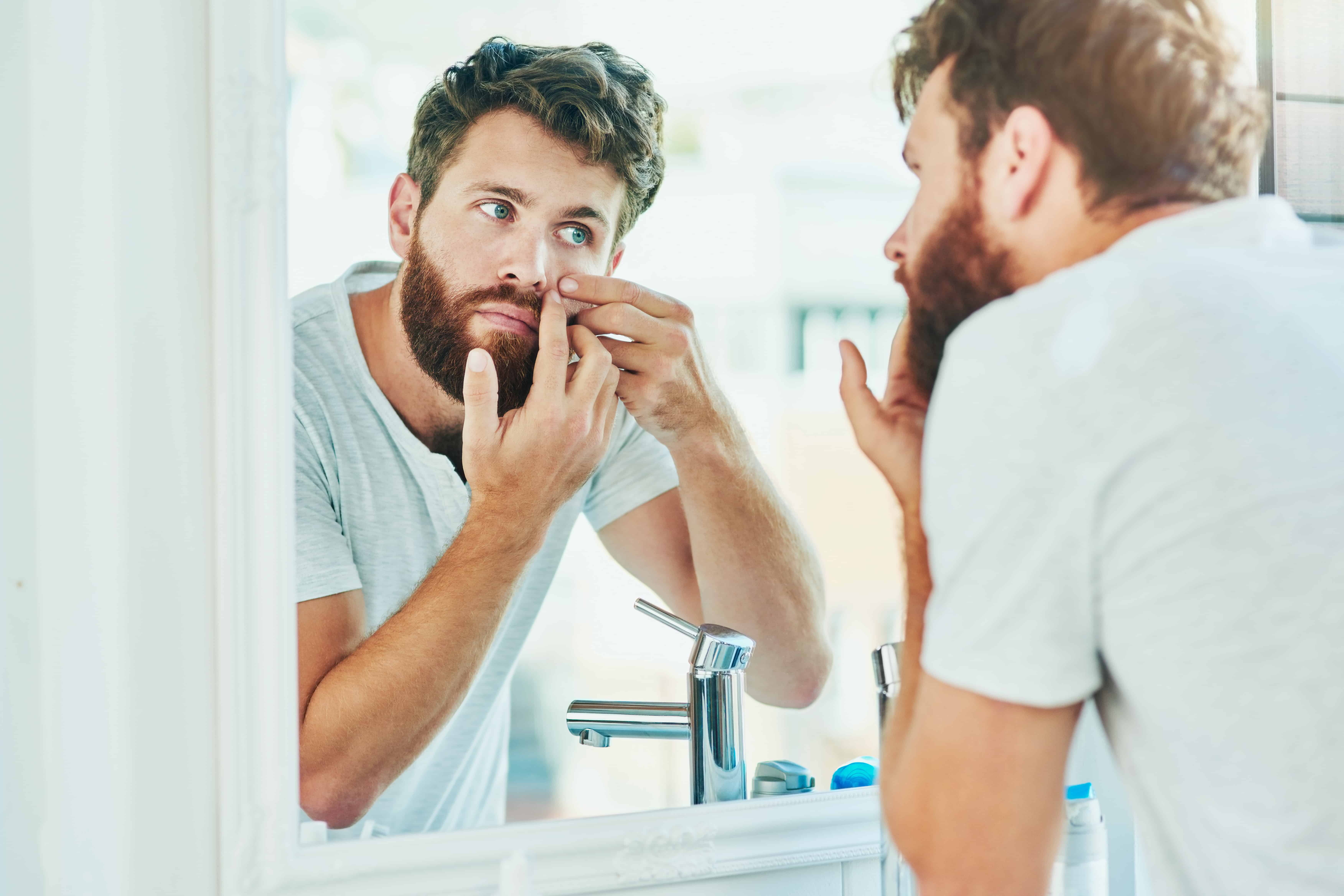Man popping pimples in the mirror